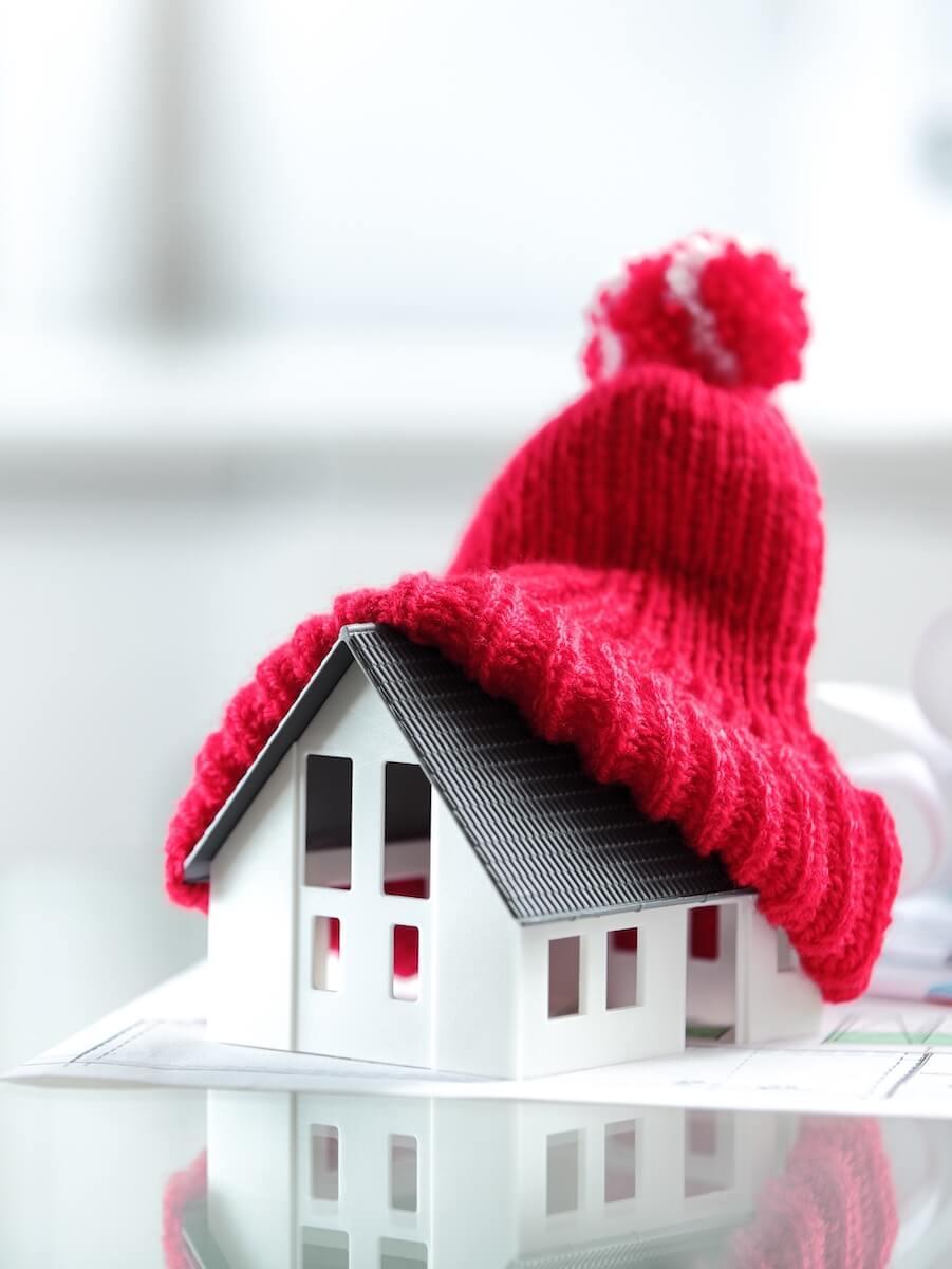 макет на къща с червена зимна шапка